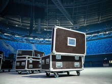 Concert Equipment Boxes. Stage Equipment In Transport Boxes. Black Wardrobe Trunks On Wheels. Equipment Boxes On Concert Stage. Stadium Stands In Background. Concept - Preparation For Concert.