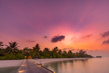 Sunset On Maldives Island, Luxury Resort Hotel And Wooden Pier Jetty. Wonderful Colorful Sky Clouds And Beach Sea Horizon. Summer Romantic Vacation Holiday, Travel Concept. Paradise Sunset Landscape