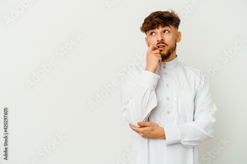 Slika na platnu Young Moroccan man wearing a typical arab clothes isolated on white background relaxed thinking about something looking at a copy space
