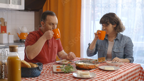 Fototapeta Young couple having Turkish breakfast at home. The couple who have breakfast by drinking Turkish tea or coffee like the color and smell of tea. Turkish breakfast concept.   obraz