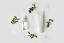 Bottles Of Serum With Green Leaves Flat Lay On White Background