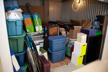 A Storage Unit Full Of Boxes And Plastic Tubs