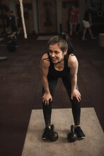 Vertical Shot Of A Sportswoman Smiling Joyfully, Resting After Working Out With Kettlebells