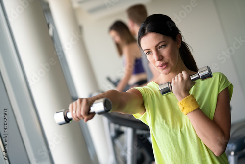 Obraz Young beautiful woman doing exercises with dumbbell in gym - fototapety do salonu