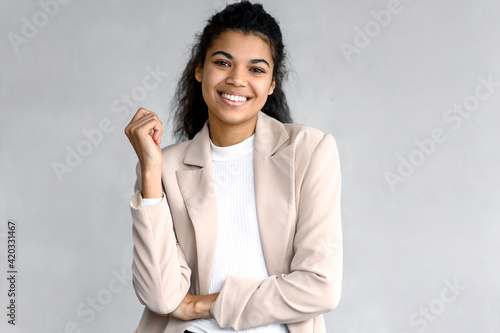 Fototapeta Portrait of elegant happy business woman or student in stylish formal suit. Beautiful young female is standing on isolated background, looking directly at the camera, smiling obraz