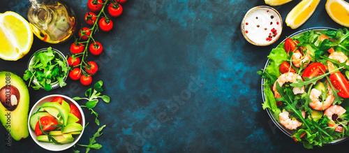 Fotografie, Obraz Fresh shrimp salad with tomatoes, lettuce, arugula, avocado, cucumber and lemon dressing on blue background