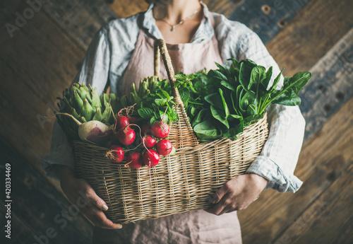Canvastavla Woman farmer holding basket of fresh vegetables and greens