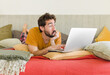 young bearded man on a bed with a laptop