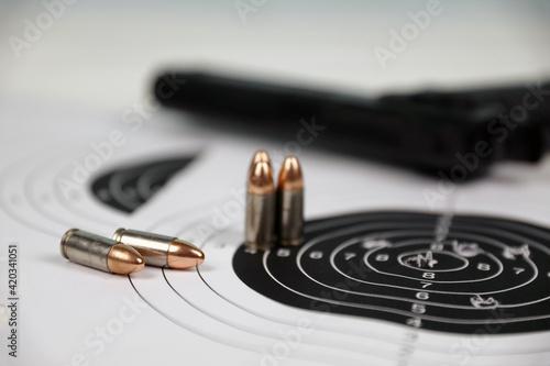 Fotografija Gun and many bullets shooting targets on white table in shooting range polygon