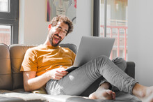 Young Bearded Man With Cheerful, Carefree, Rebellious Attitude, Joking And Sticking Tongue Out, Having Fun With A Laptop On A Couch Laptop Concept