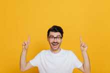 Handsome Caucasian Cheerful Young Man In White Basic T-shirt And Glasses Amazed Looks At The Camera And Points Fingers Up At Empty Space, Stands On Isolated Orange Color Background