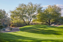 Beautifully Manicured Golf Course With Cart Path Rolling Over Green Hill On A Blue Sky Day
