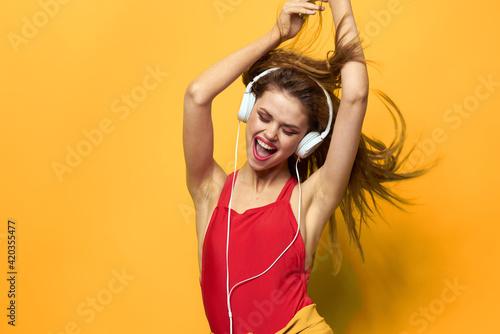 Obraz Emotional woman in white headphones listens to music fun lifestyle yellow background - fototapety do salonu