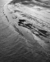 Vertical Shot Of Small Waves At A Sandy Beach During Low Tide In Belgium