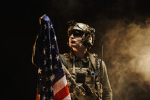 Special Forces Soldier Holding US National Flag In The Dark