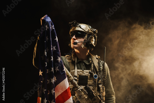 Photographie Special forces soldier holding US national flag in the dark