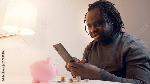 Tela Online shopping, Young african american black man using smartphone for online shopping and paying with credit card
