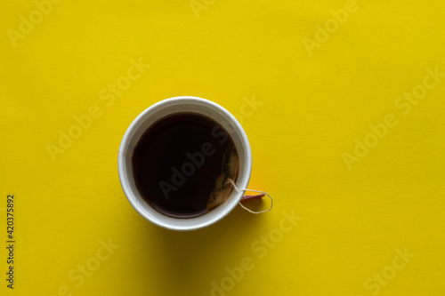 Foto A disposable white cup full of tea, yellow background