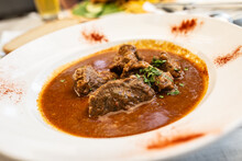 Beef Stew With Large Chunks Of Meat Served In A White Plate