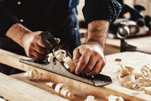 Carpenter's Hands Planing A Plank Of Wood With A Hand Plane