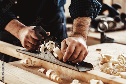 Carpenter's hands planing a plank of wood with a hand plane Fototapet
