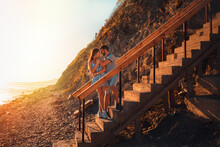A Young Couple Of Lovers Embrace Standing On The Stairs And Pose Against The Background Of The Sea And Sunset. The Concept Of Valentine's Day