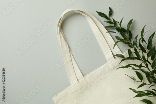 Eco bag and twig on light gray background Fototapeta