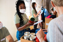 Group Of Volunteers With Face Mask Working In Community Charity Donation Center.