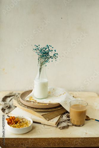 Fototapeta stylish simple monochrome beige table setting at home. gypsophila in glass bottle of milk on stack of old books, cup of coffee, plate of oatmeal, cotton napkins. creating comfort in interior obraz