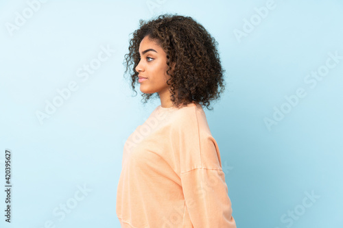 Obraz Young African American woman isolated on blue background in back position and looking back - fototapety do salonu