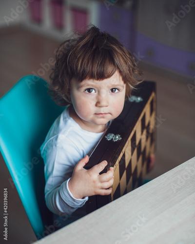 Mała dziewczynka z szachownicą. Dziecko uczy się grać w szachy. - fototapety na wymiar