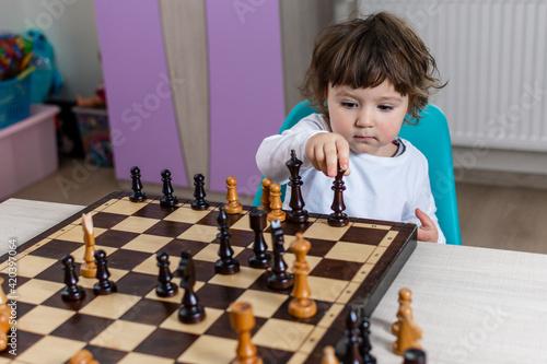 Fototapeta Mała dziewczynka z szachownicą. Dziecko uczy się grać w szachy. obraz