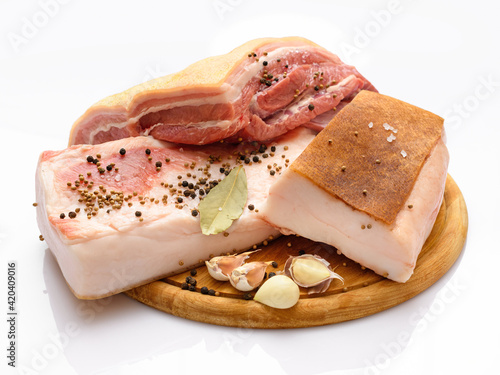 raw pork meat and lard with salt, spices and garlic on a cutting board, white ba Fototapeta