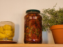 A Jar Of Pickled Dried Tomatoes On A Shelf, Next To A Potted Plant And A Jar Of Preserved Lemons. Focus On The Jar With Tomatoes