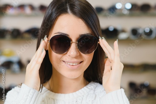 Obraz Which one is better fit me. Portrait of cheerful hesitating woman in optician store, making decision, holding stylish sunglasses, choosing what she should buy. Great discounts for buying two pairs - fototapety do salonu