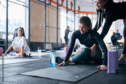 Obraz Helpful instructor guiding women experience at the gym - fototapety do salonu