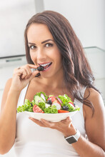 Beautiful Woman Biting Into An Olive Taken From A Healthy Salad In Her Other Hand