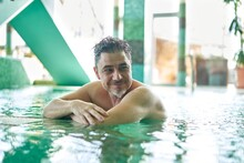 Man Relaxing In Swimming Pool. Concepts Of Spa, Wellness.
