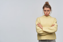 Portrait Of Sad, Adult Girl With Blond Hair Gathered In Bun. Wearing Yellow Sweater. Keeps Arms Crossed And Pouts Her Lip. Watching To The Left At Copy Space, Isolated Over White Background