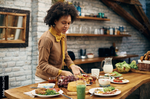 Fototapeta African American woman serving food at dining table. obraz