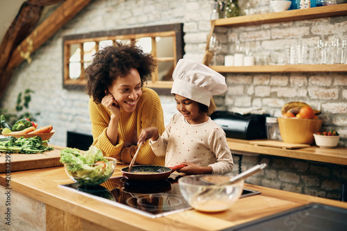 Obraz na plátně Happy black mother and daughter enjoying while preparing food in the kitchen