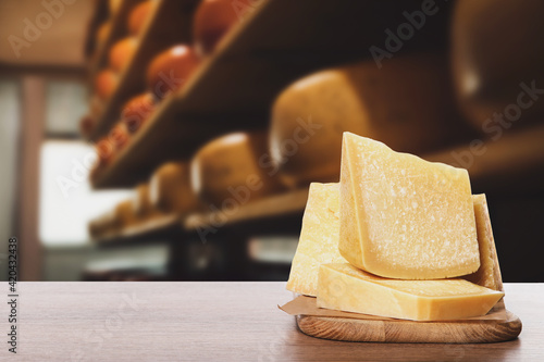 Fototapeta Delicious parmesan cheese on wooden table in warehouse, space for text obraz