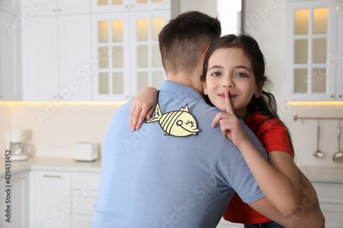 Fototapeta Cute little girl sticking paper fish to father's back at home obraz