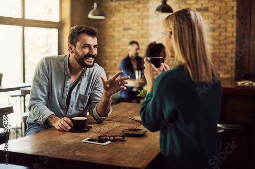 Obraz Happy couple talking while drinking coffee in a cafe. - fototapety do salonu