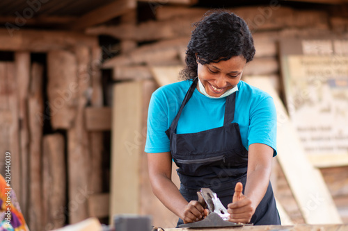Canvas Print female african carpenter working in her workshop, wearing a face mask on her chi