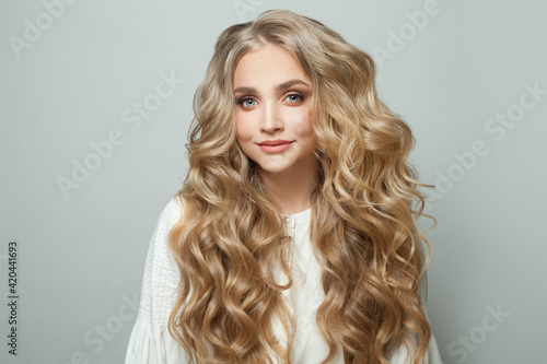Foto Attractive blonde woman with long perfect hair looking at camera and smiling on