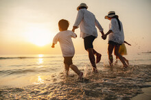 Happy Asian Family At Consisting Father, Mother,son And Daughter Having Fun Playing Beach In Summer Vacation On The Beach.Happy Family And Vacations Concept.