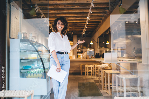 Half length portrait of prosperous Caucaisan manager feeling success in franchise coffee shop standing in doorway and smiling at camera, happy self employed woman greeting in local cafeteria industry