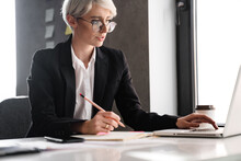 White-haired Puzzled Woman Writing Down Notes While Working With Laptop