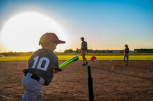 Youth Batter Hitting A Tee Ball Into An Open Field At Practice